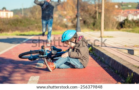 Boy in the street ground with a knee injury screaming after falling off to his bicycle - stock photo