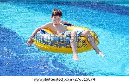 Boy in the swimming pool on inner tube