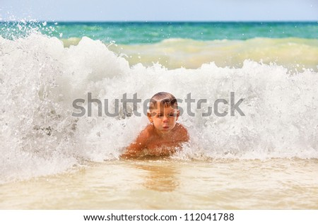 boy in the waves breaking on the shore of beach - stock photo