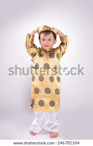 Boy in traditional Vietnamese dress. Lunar new year on white background. Happy Asian baby boy wearing Ao Dai suit in studio. Tet Holiday.
