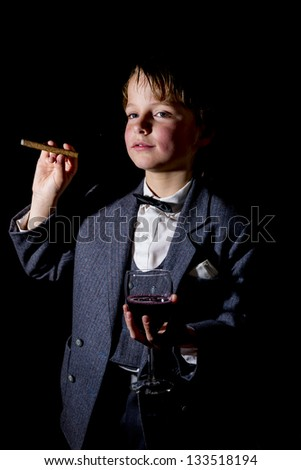 boy in tuxedo, with glass of red wine and a cigar - stock photo