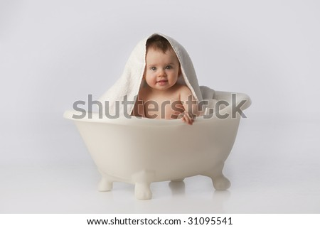 Boy in white bath tub with towel on head