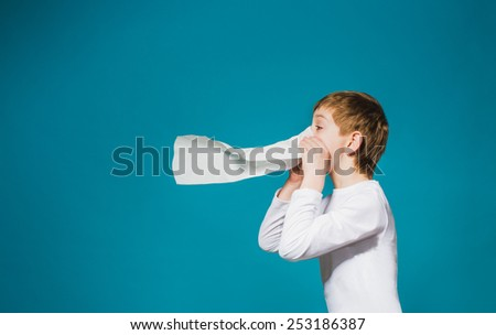 Boy in white clothes comical blowing his nose