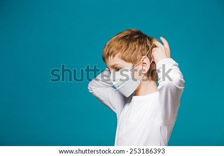 Boy in white putting on protection mask
