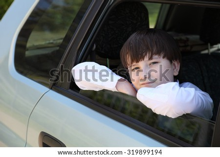 Boy in white shirt and tie in the car - stock photo