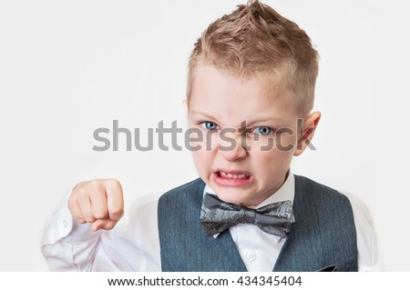 boy in white shirt, waistcoat and bow tie furious with clenched teeth swung his fist on an isolated background - stock photo