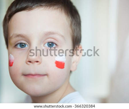 boy in white shirt with polish flag on his cheeks  - stock photo