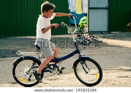 Boy in white t-shirt ride on bike outdoors against green wall - stock photo