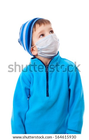 Boy in winter clothes and protective medical mask looking sideways, isolated on white