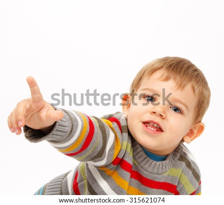 Boy in winter clothes pointing towards something - stock photo