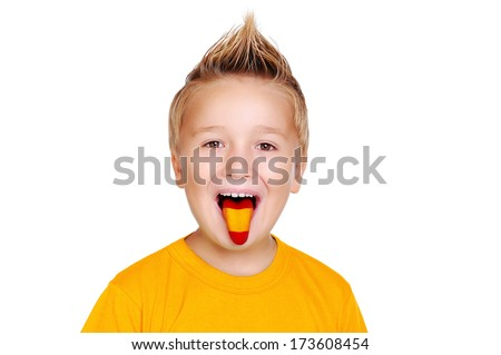 boy in yellow shirt with spanish  flag on his tongue - stock photo