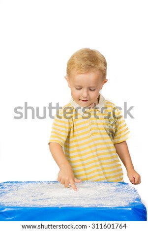 Boy in yellow t-shirt draws a finger on the table with flour