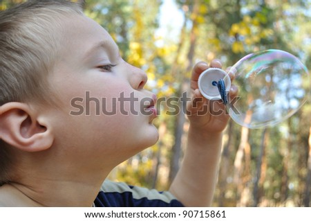 Boy inflates the bubble, the background-forest
