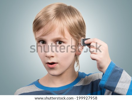 Boy inserting SD card into his head - stock photo
