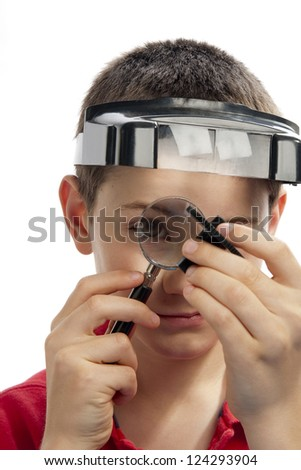 boy inspecting a gear using a magnifying glass. - stock photo
