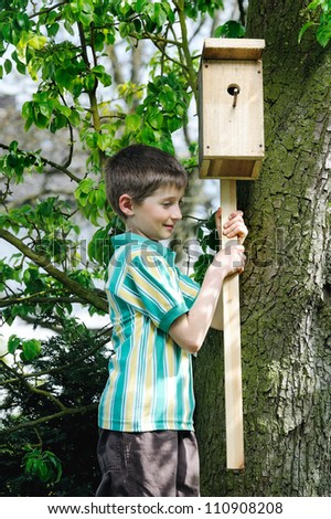 Boy installing a self-made Bird House. - stock photo