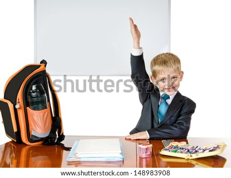 boy is at the table with satchel and school belongings - stock photo