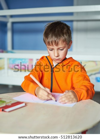 Boy is carefully drawing a picture with pencils. He is five years old. He is sitting at the table.