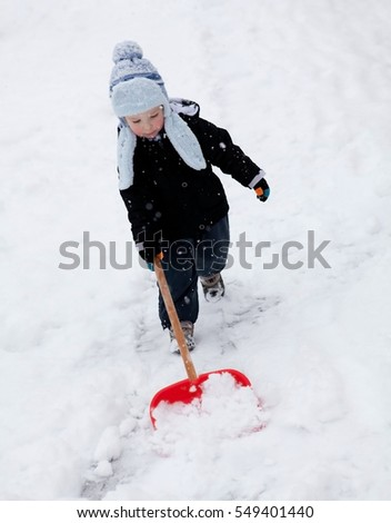 boy is cleaning snow after snow calamity