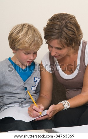 Boy is doing his homework in the livingroom while mother is helping him