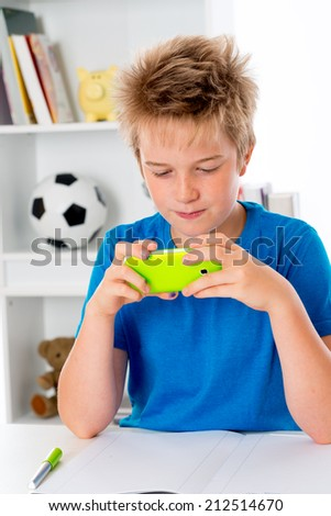 boy is doing homework and using his smartphone - stock photo