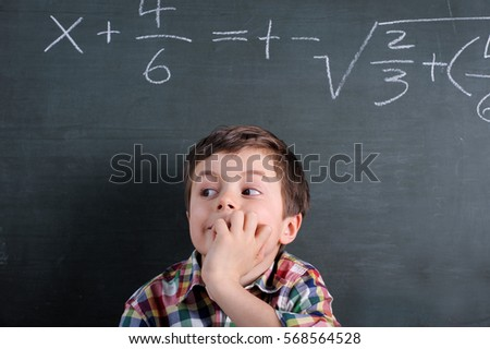 Boy is having difficulties solving a mathematical problem on blackboard in elementary school