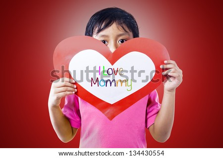 Boy is holding a love card for his mommy - stock photo
