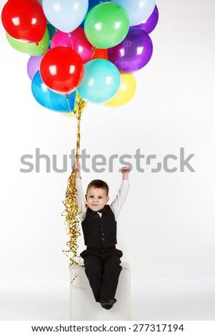 Boy is holding colorful balloons - isolated over a white background - stock photo