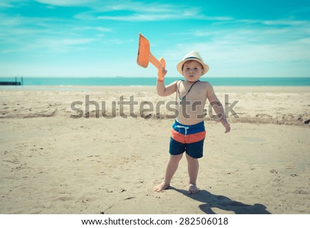 boy is holding his shovel in the air on the beach - stock photo