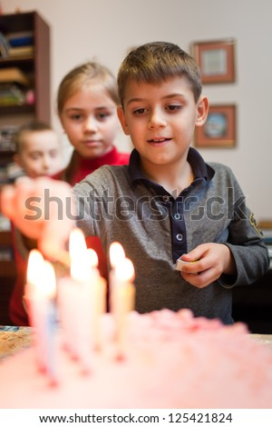 Boy is lighting the birthday cake candles - stock photo