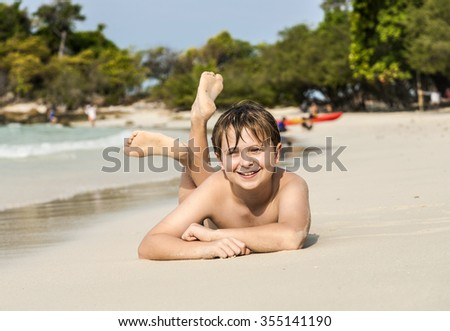 boy is lying at the beach and enjoying the warmness of the water and looking self confident and happy