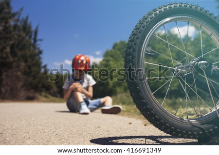 Boy is lying hurt after a bicycle accident. Kids safety concept. Selective focus toned image with shallow depth of field