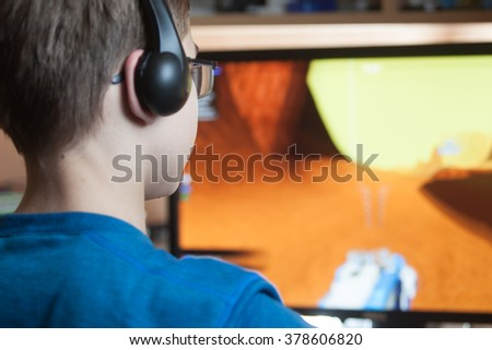 Boy is playing a computer game at home - stock photo