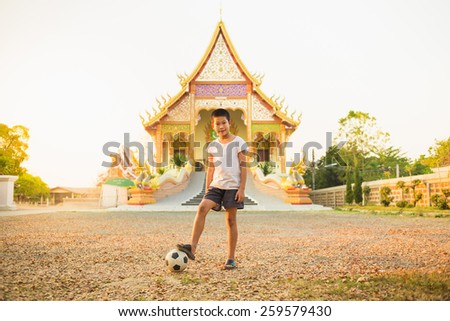 boy is playing football at the temple - stock photo