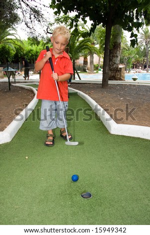 Boy is playing golf - stock photo