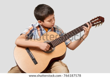 Boy is playing the acoustic guitar