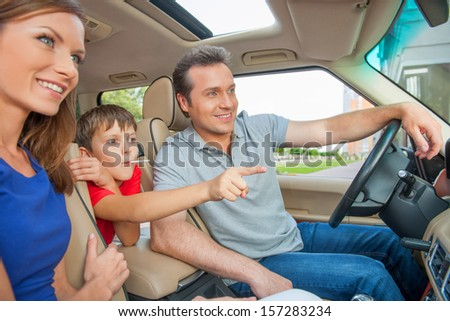 Boy is pointing his finger on something while sitting a car with his family - stock photo