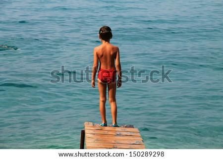 Boy is ready to jump into the sea , Croatia moments - stock photo
