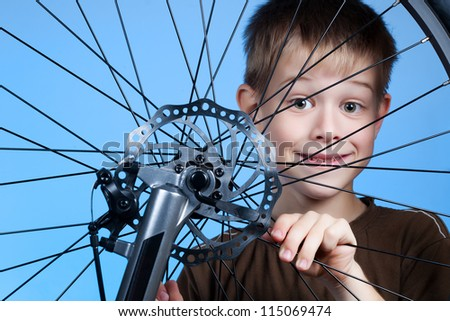 Boy is repairing the bicycle wheel - stock photo