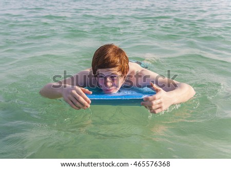 boy is surfing on a small surfboard in a beautiful sea with crystal clear water and blue sky