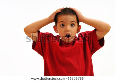 Boy is surprised and shocked; puts hands on head in disbelief. - stock photo