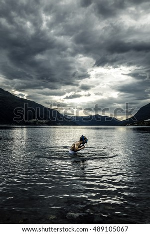 Boy is swimming in lake of Norway