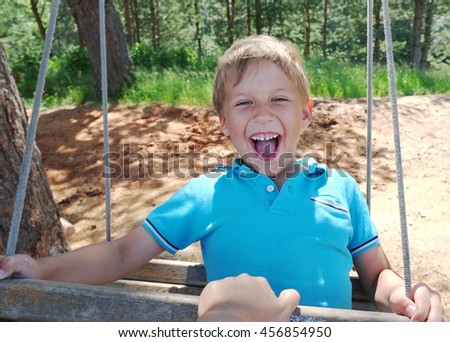 Boy is swinging and smiling  - stock photo