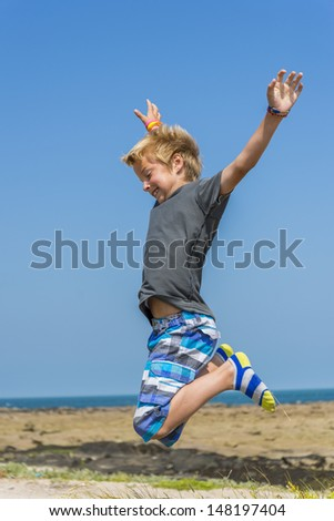 boy jumping for joy near the sea - stock photo