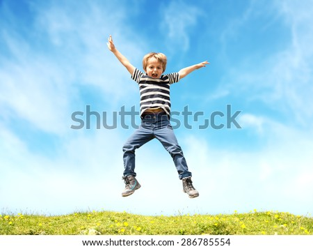 Boy jumping in a meadow at the top of a hill against a blue sky - stock photo