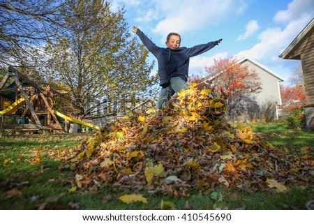 Boy jumping in a pile of autumn leaves  - stock photo