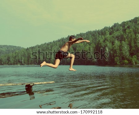 boy jumping in lake at summer vacations - vintage retro style - stock photo