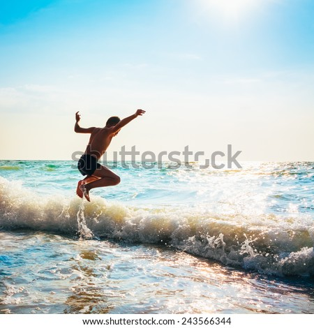 Boy Jumping In Sea Waves. Jump Accompanied By Water Splashes. Summer Sunny Day, Ocean Coast - stock photo