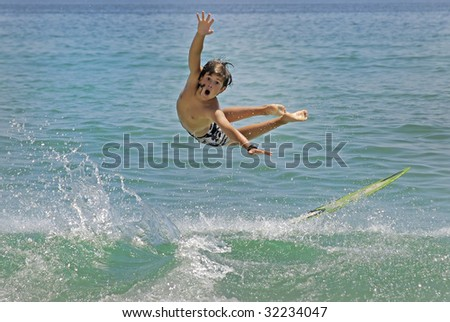 Boy jumping in the air with skimboard in the sea - stock photo