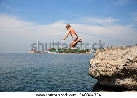 Boy jumping into the sea from the old pier. Embankment in Vladivostok, Russia.